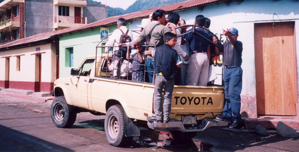 Photo of Guatemalen people riding in the back of a pickup truck